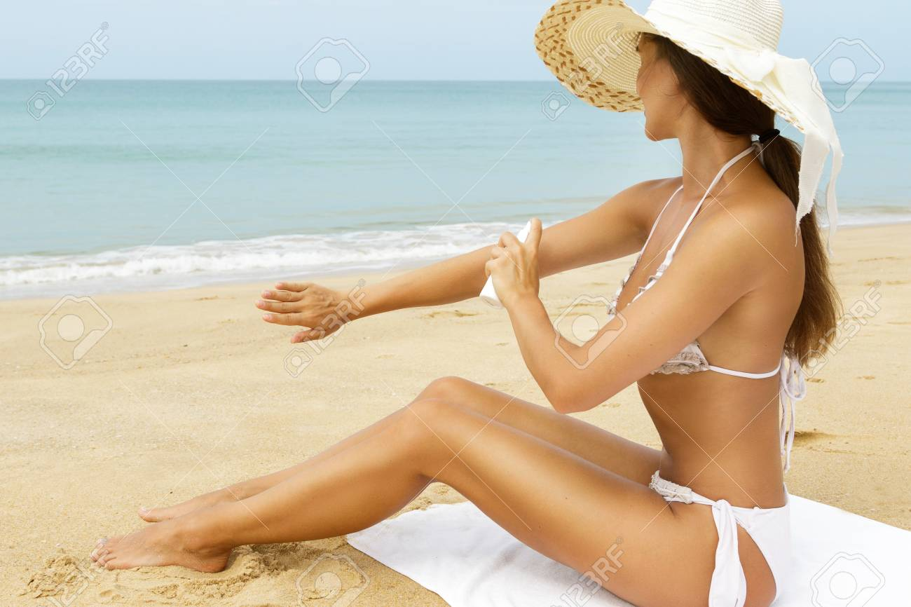 Beautiful Woman In Hat Sitting On The Beach And Applying Sunscreen.. Stock  Photo, Picture And Royalty Free Image. Image 105351756.