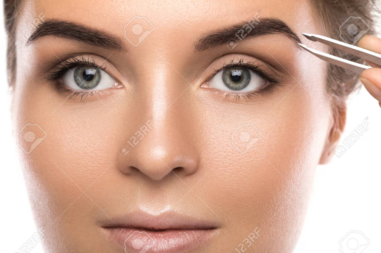 Close up of female face and eyebrow with tweezers - 106930223