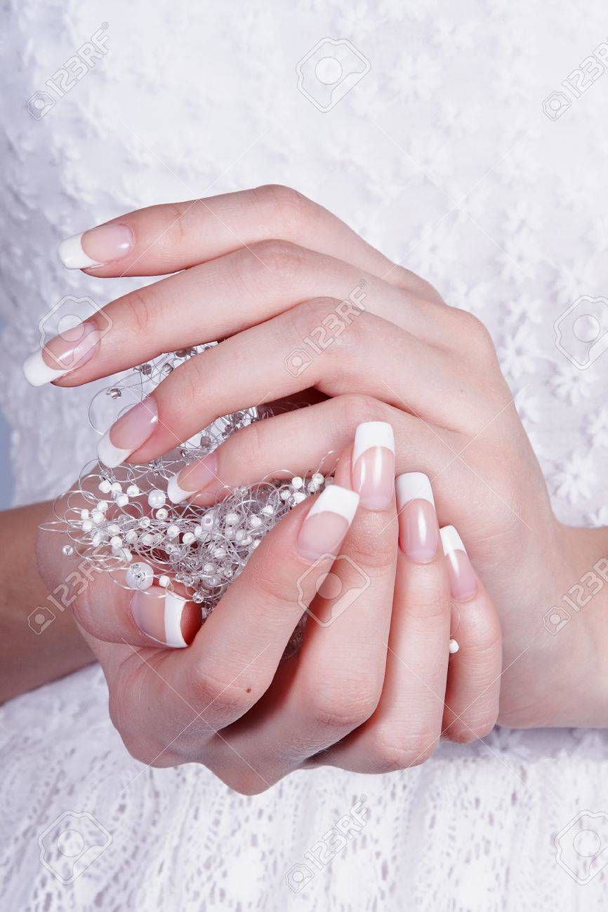 Beautiful female hands with manicure against a white dress Standard-Bild - 14095917