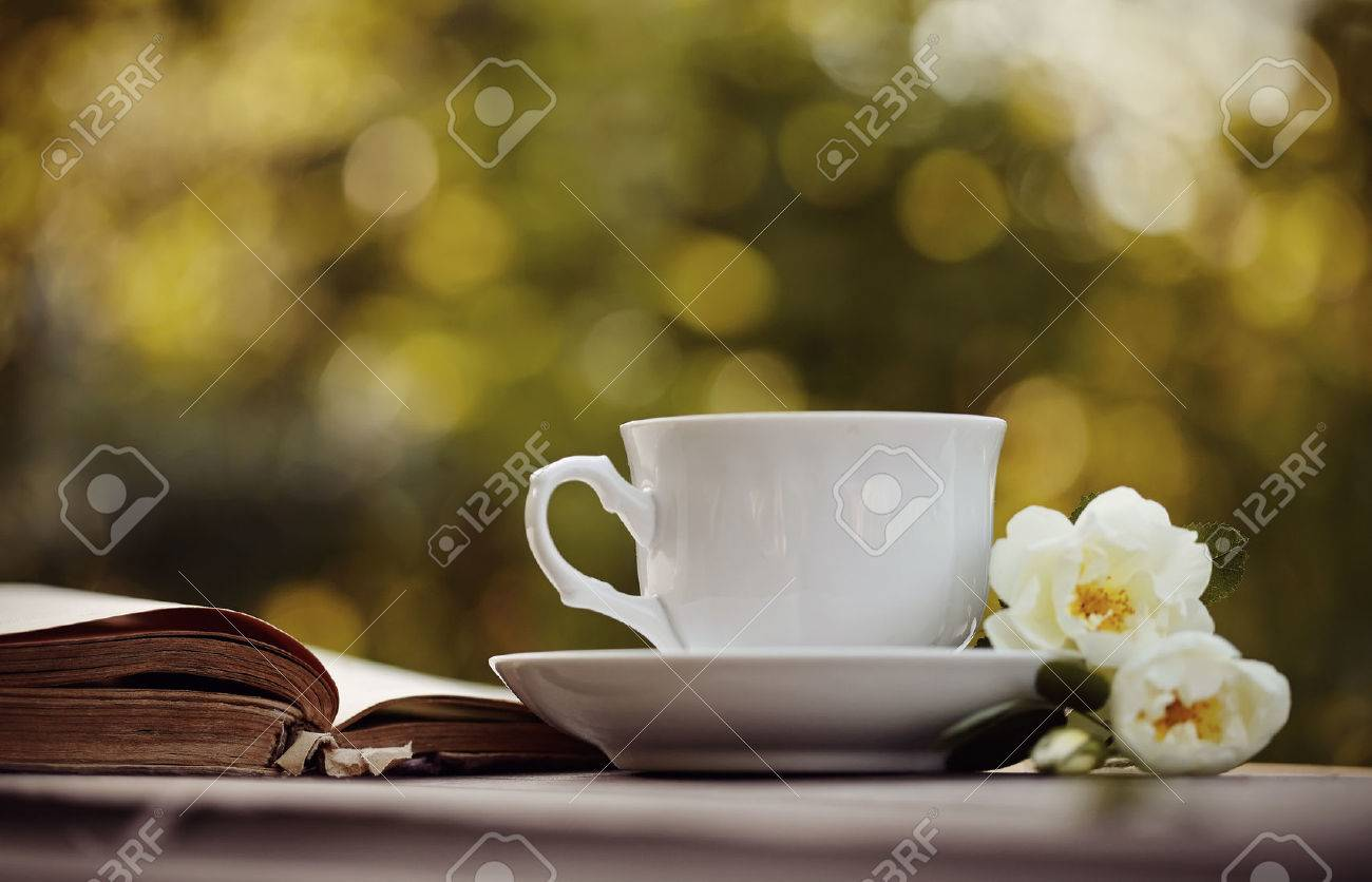 Old open book and a white cup with a wild roses on a table. Standard-Bild - 59124369