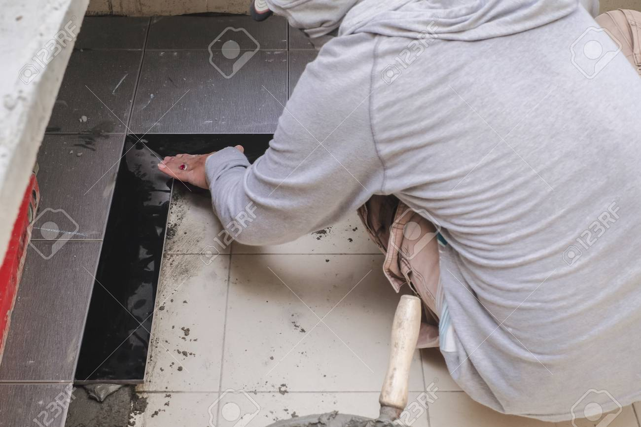 Construction Worker Tiler Is Installing Floor Tile At Repair Stock Photo Picture And Royalty Free Image Image 96817796