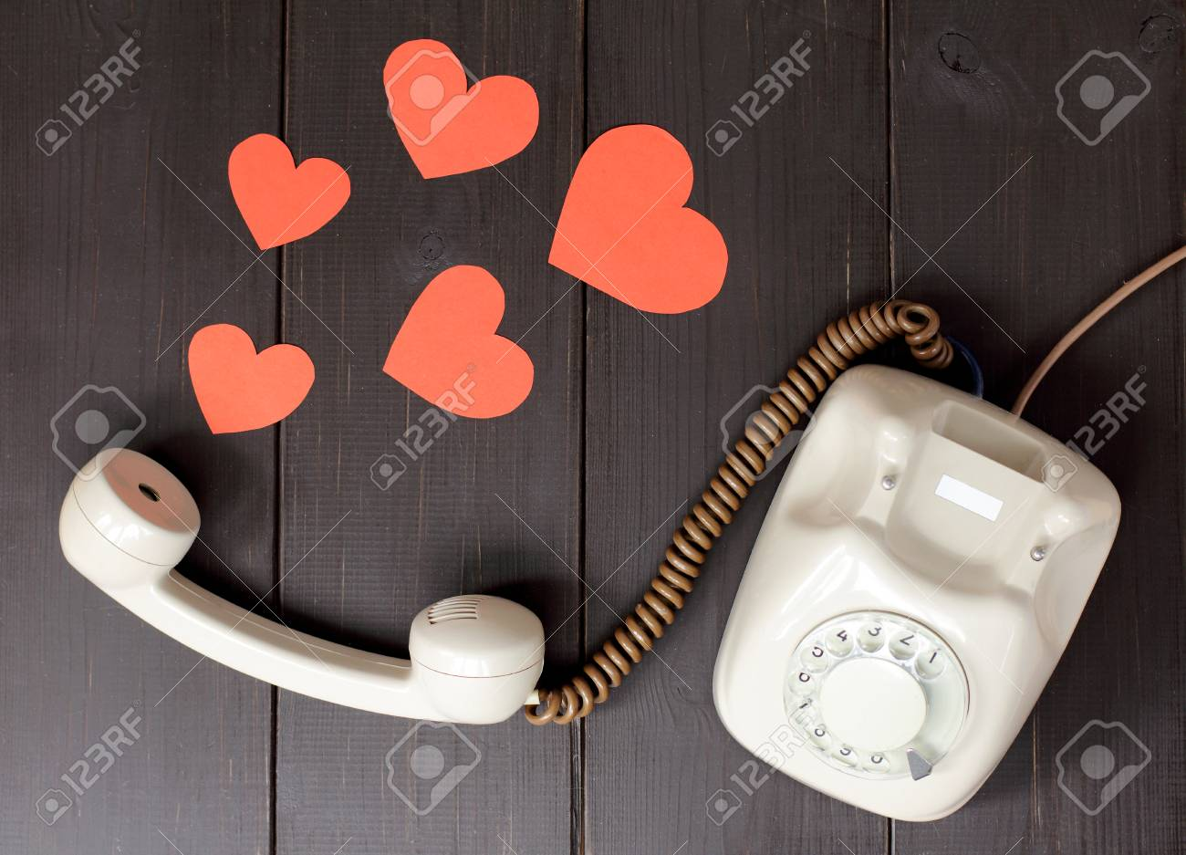idea attractive voice in the form of hearts flying out of telephone handset lying on a wooden table / amorous talking by phone - 62150739