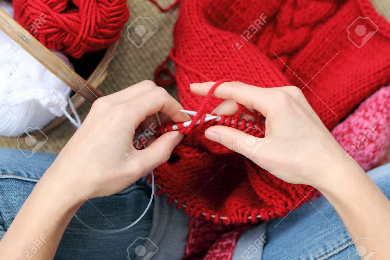 e970aec66ae9 Banque d images - Mains tricotant avec du fil rouge, des vêtements pour la  saison hivernale