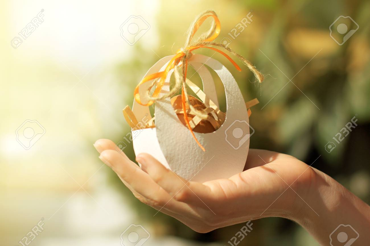 Egg in a festive package adorned with bow in hand delivery stock egg in a festive package adorned with bow in hand delivery easter gift stock photo negle Images