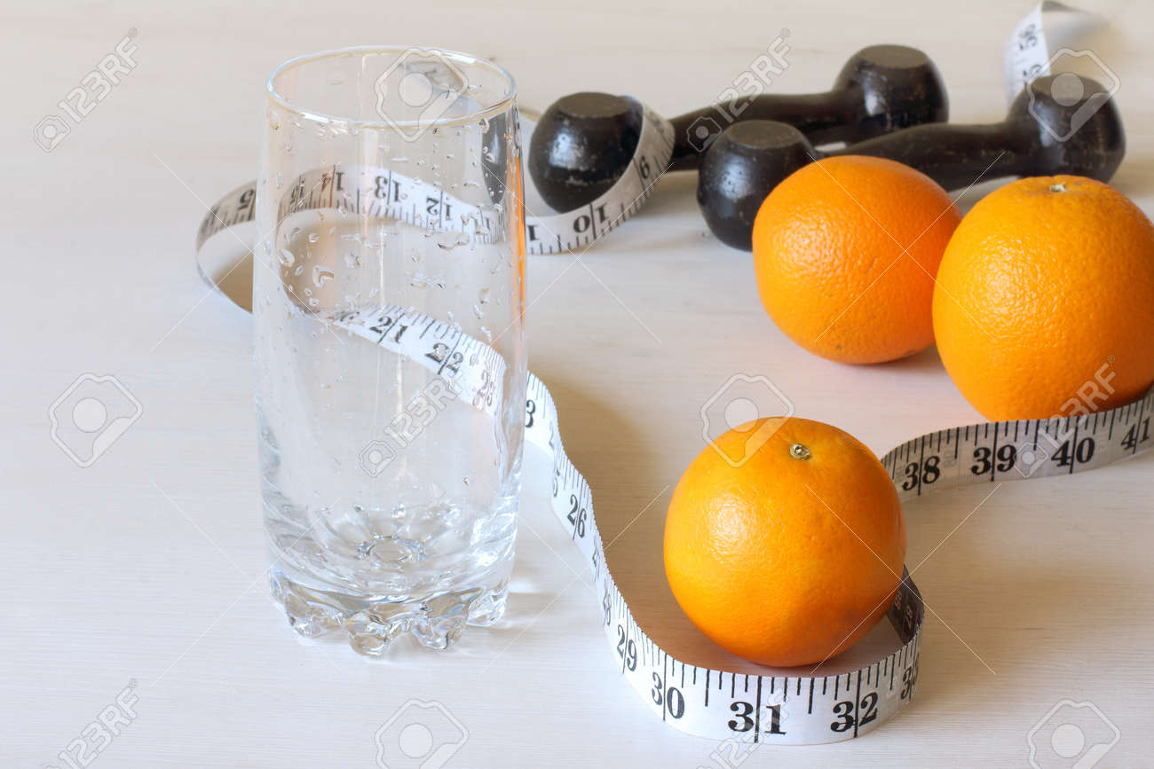 oranges, an empty glass with a measuring meter and dumbbells on the table. fruit diet and sports - 171299053