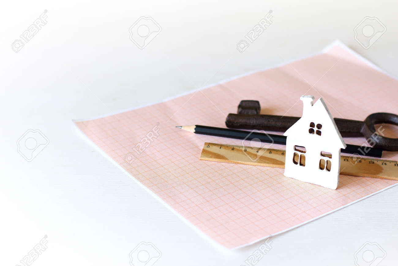 mock-up of a white house on graph paper on a background of a pencil, key and ruler. Plot Design, Construction - 171298931
