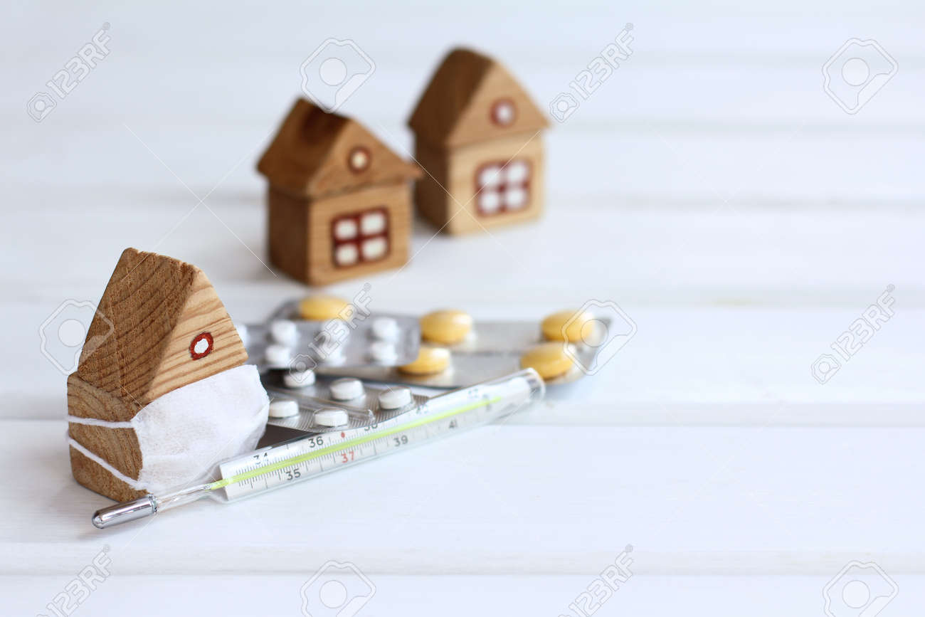 wooden house in an individual mask with a thermometer and tablets against the background of other houses. self-isolation with viral infections Disease - 171352455