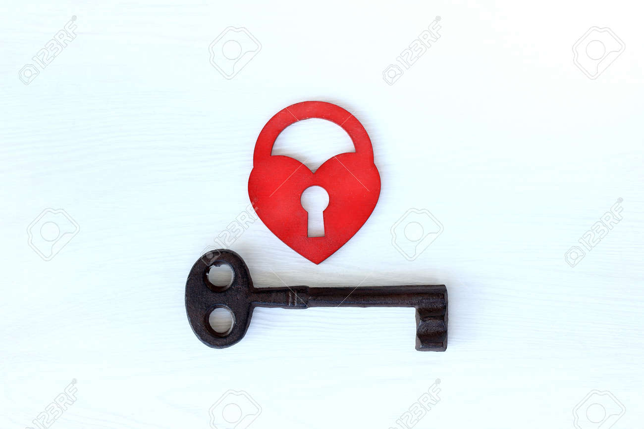 red heart in the form of a lock and a large metal key, top view. love unites different - 173003508