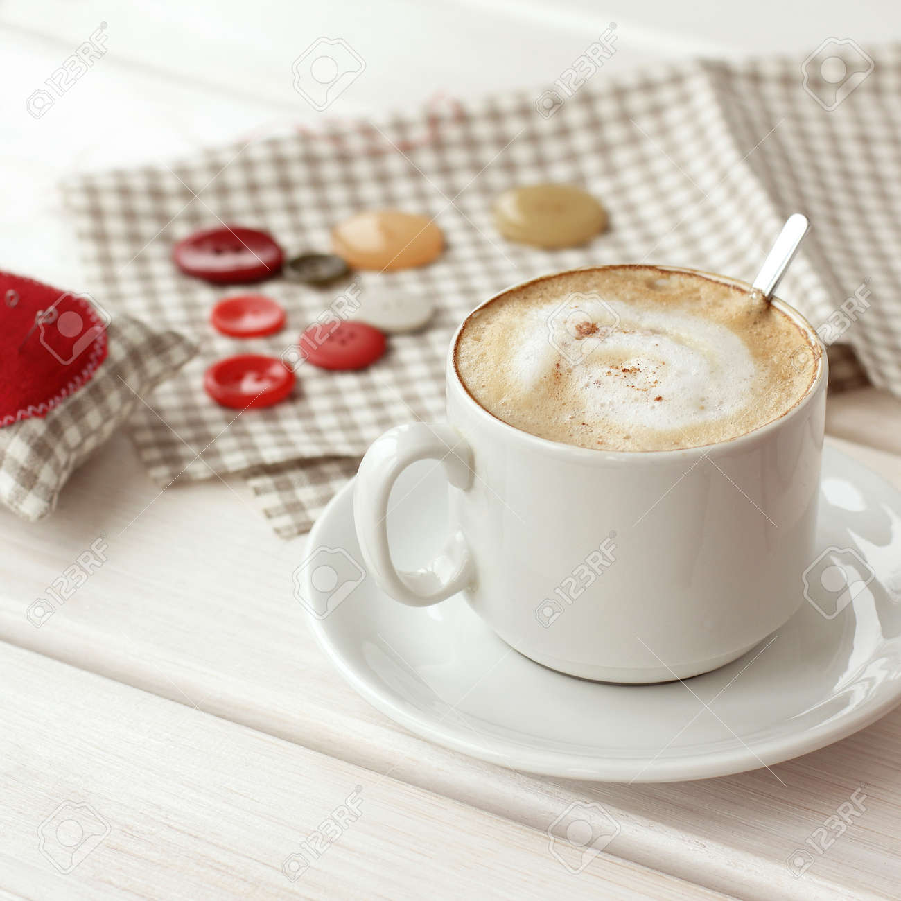 frothy cappuccino in a mug on the background of needlework on the table. home coffee break - 173004275