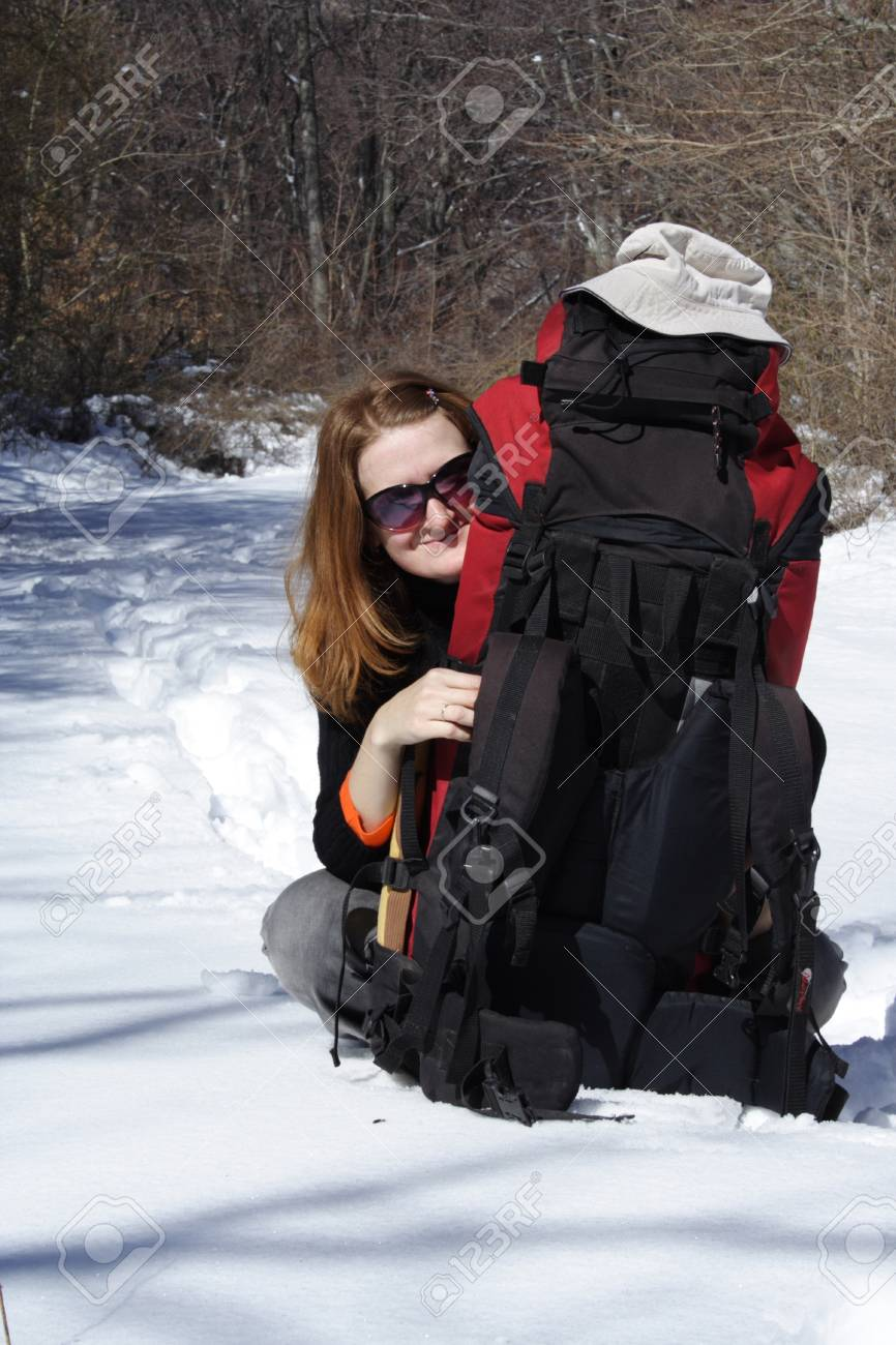 girl sitting on a snow with backpack Stock Photo - 1727725
