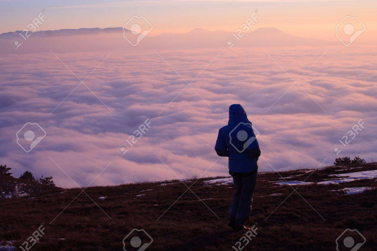 girl hiker looks at the majestic sunset and overcast clouds below Stock Photo - 2553297