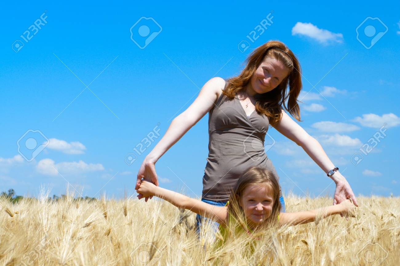 mother holding a hands of daughter at the wheat field Stock Photo - 5137364