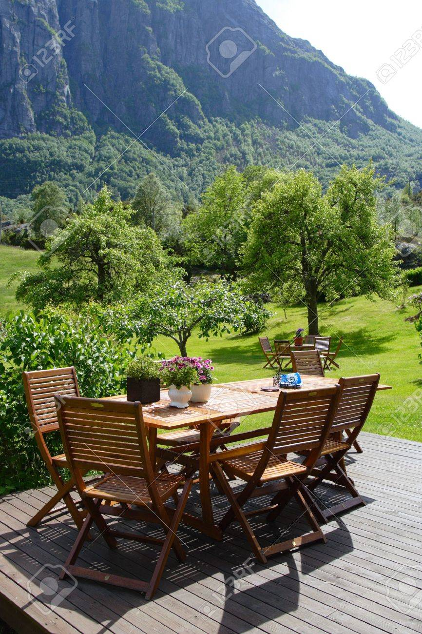 table and chairs standing at the garden and mountains in the background Stock Photo - 7920877