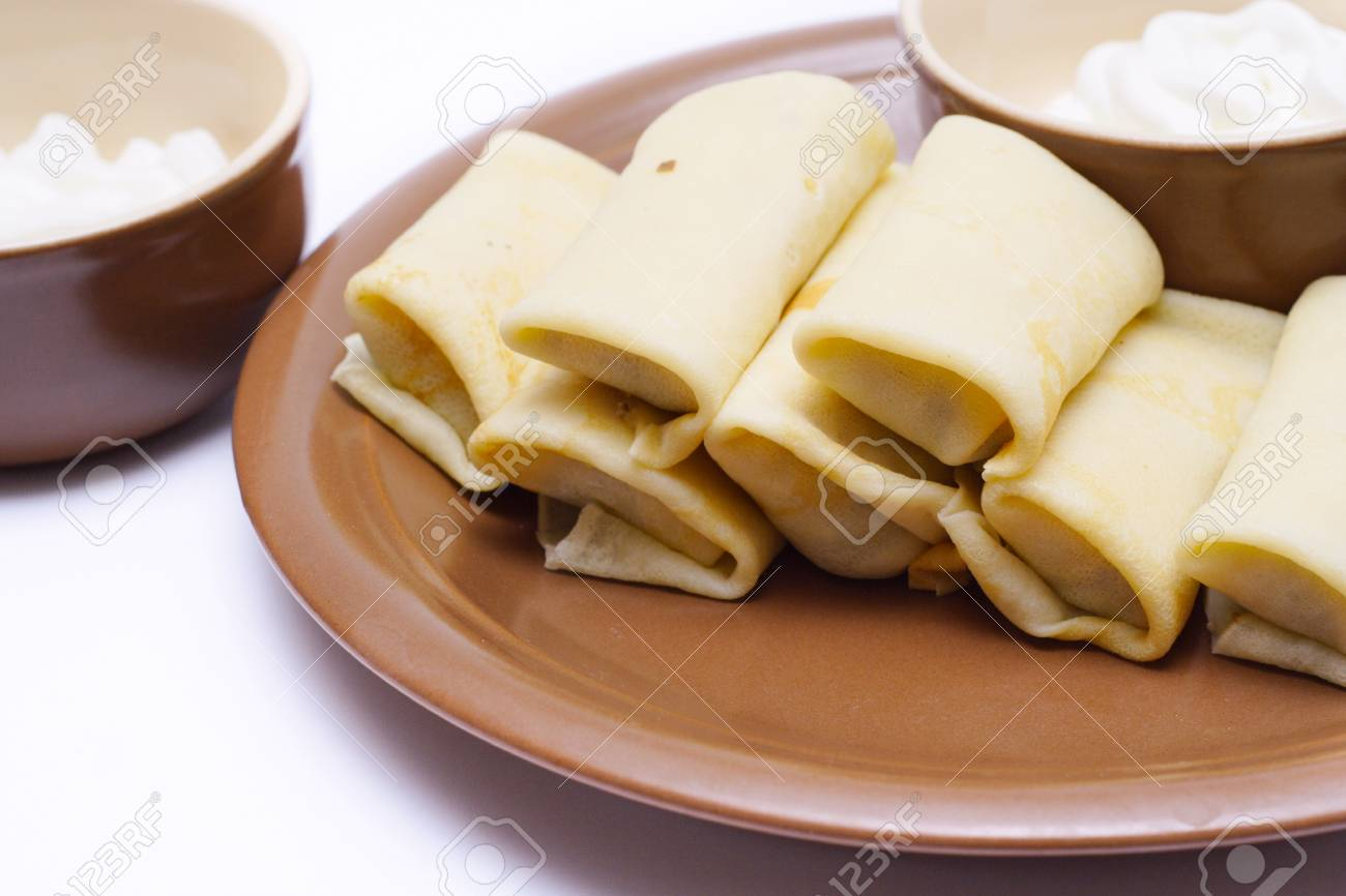 dish full of russian pancakes with sour cream at saucer Stock Photo - 23536468