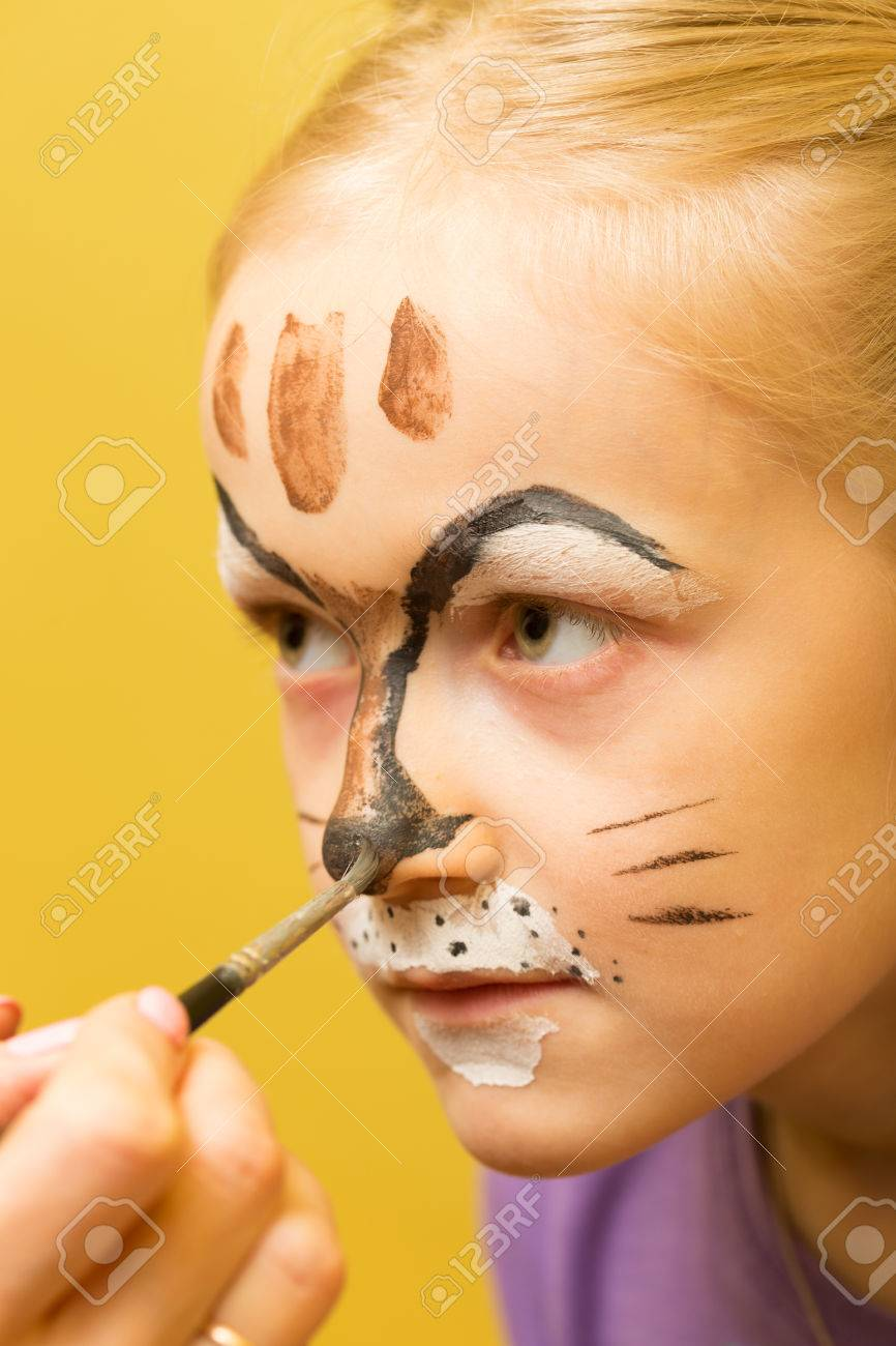 mother painting a face of her daughter like girl cat