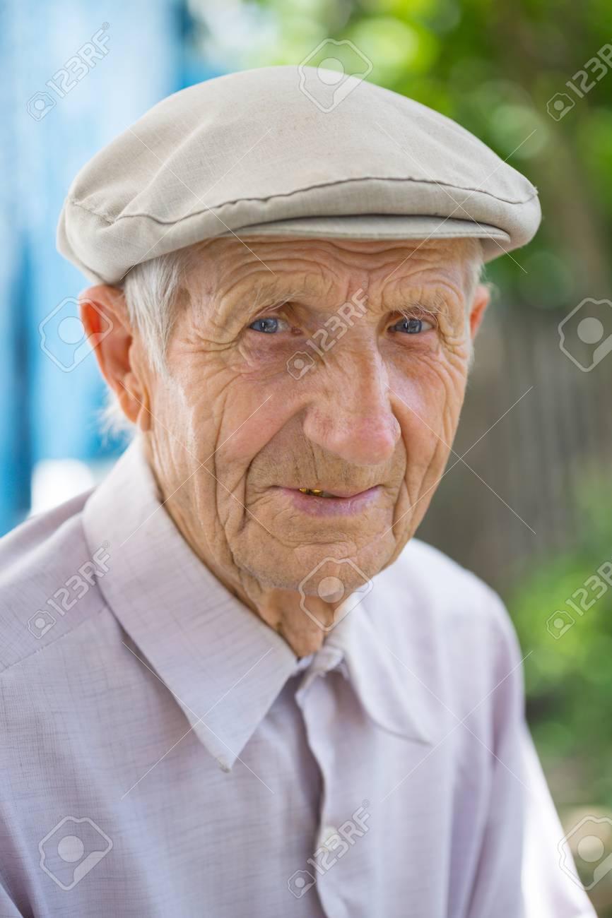 portrait of senior man sitting near his house in the village - 102471633
