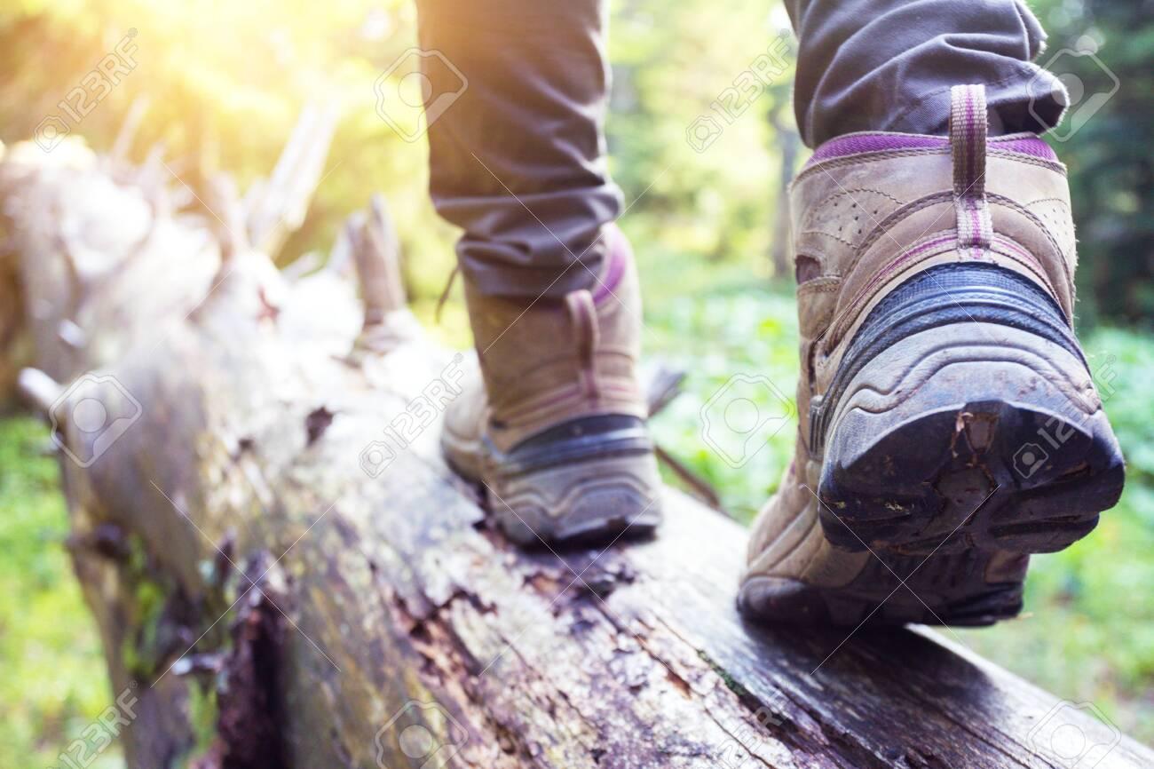 hiking boots close-up  girl tourist steps on a log