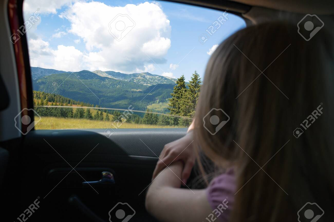 Summer Road Trip. Happy beautiful girl traveling in a car across at the mountains. Romania - 129685084
