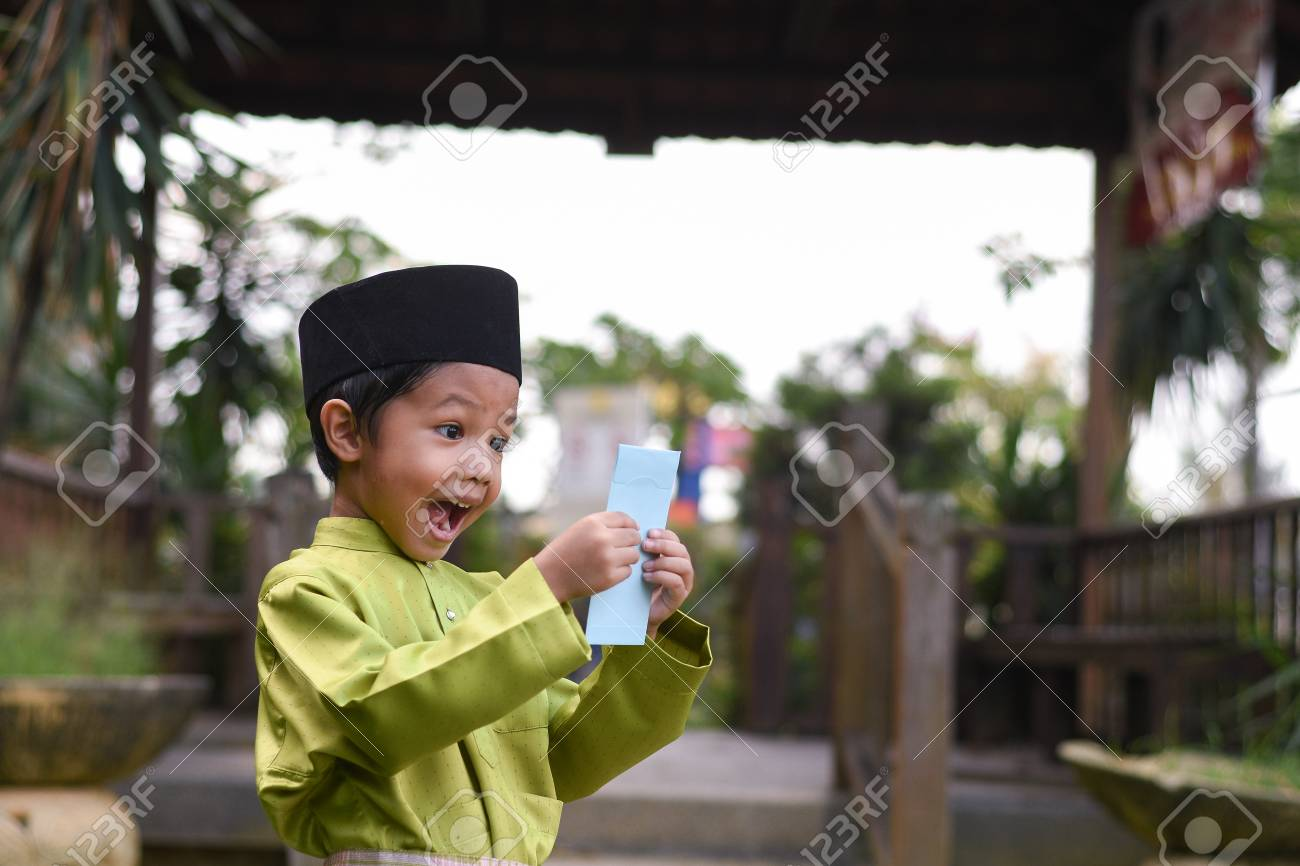 A Malay boy in Malay traditional cloth showing his happy reaction after received money pocket during Eid Fitri or Hari Raya celebration. - 102639554