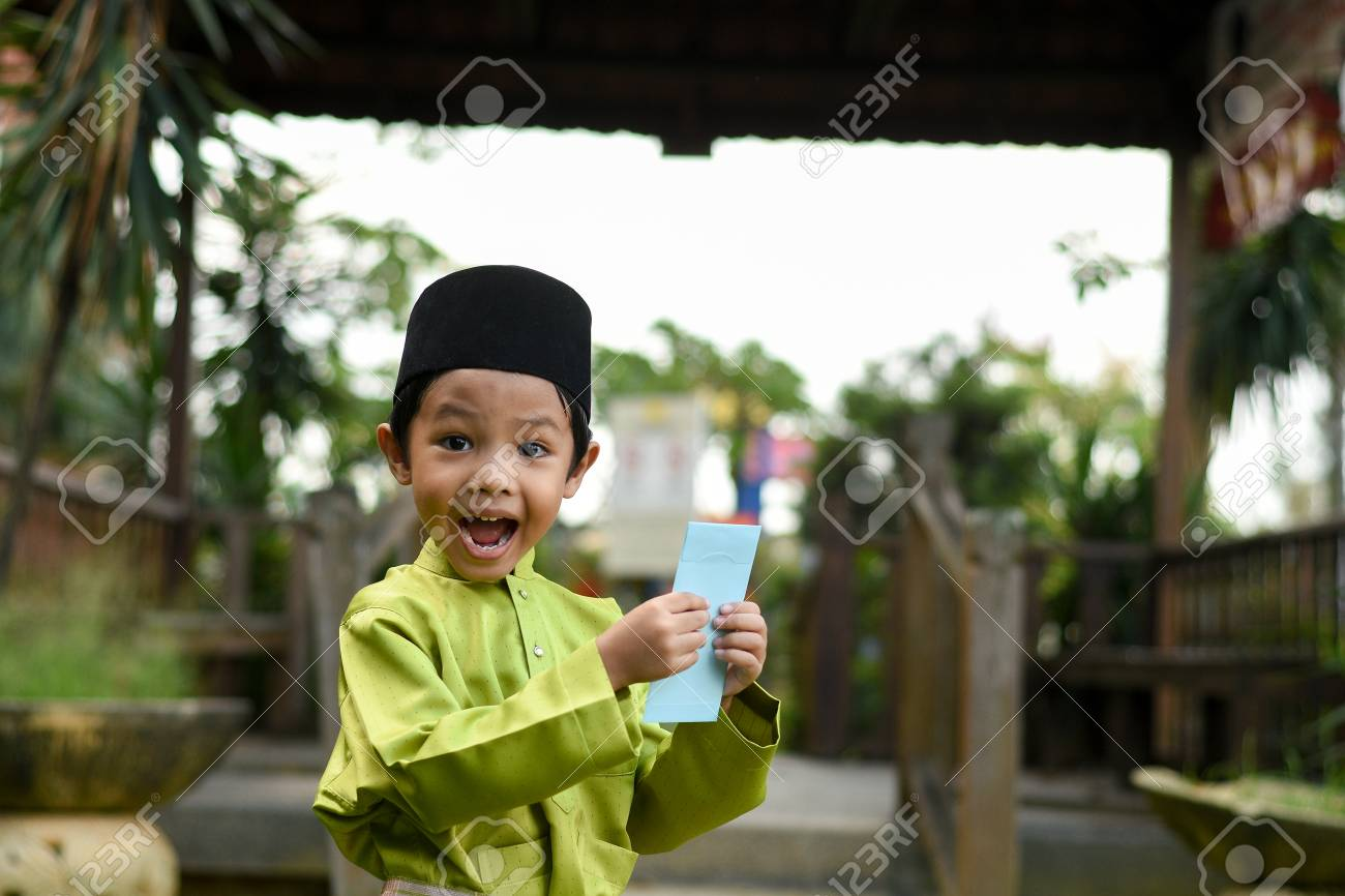 A Malay boy in Malay traditional cloth showing his happy reaction after received money pocket during Eid Fitri or Hari Raya celebration. - 102639558