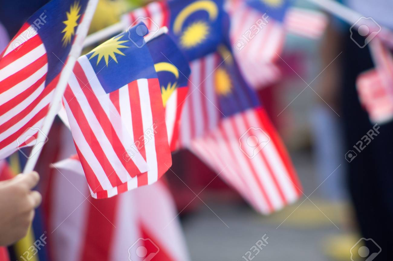 Hand waving Malaysia flag also known as Jalur Gemilang in conjunction with the Independence Day celebration or Merdeka Day. - 106620086