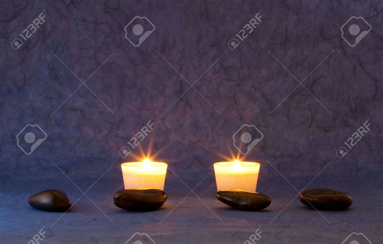 A set of massage stones on blue/purple wallpaper with candles Stock Photo - 5347921