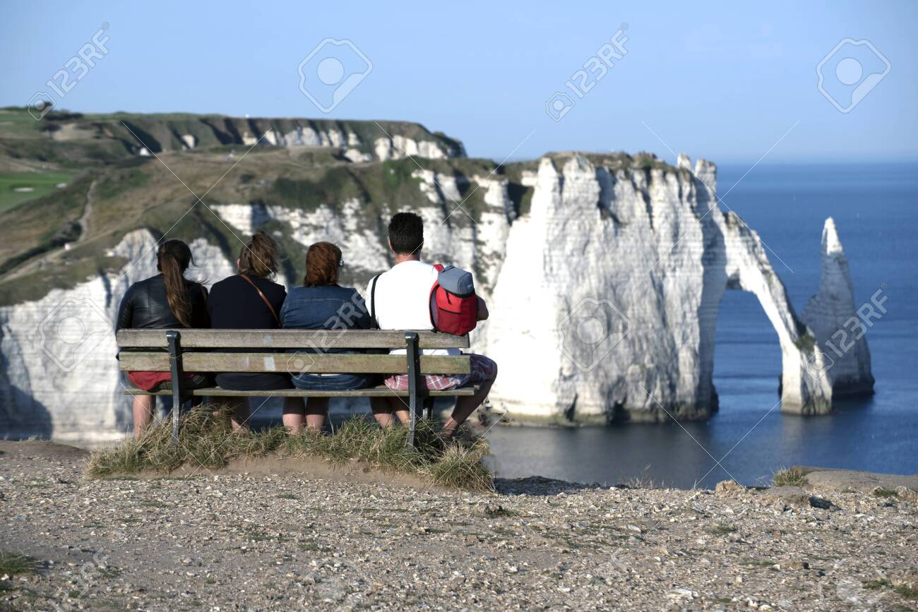 Four People Enjoying The Views Of The Cliffs Of Etretat Normandy