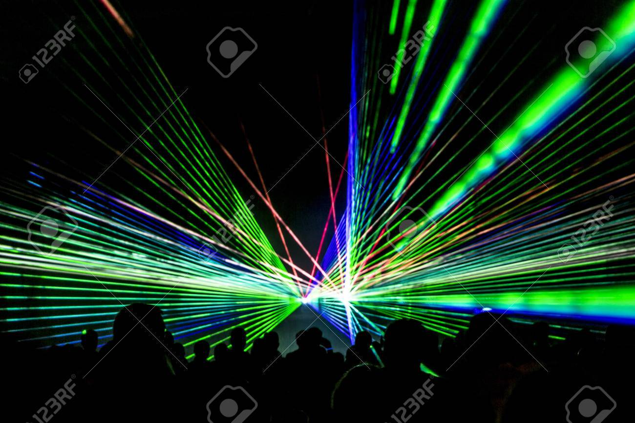 Laser show rays stream. Very colorful show with a crowd silhouette and great laser rays on pyrotechnic festival in germany. - 66520706