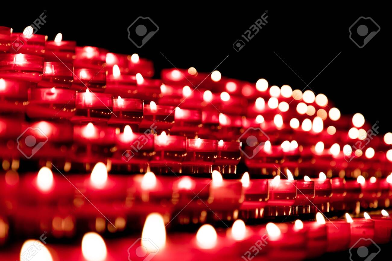 Group of red candles in church for faith resurrection prayer. Candlelight fire flames in rows are silent religion symbol for peace, life and soul. Obituary hope sacrifice against sorrows and pain. - 144216729