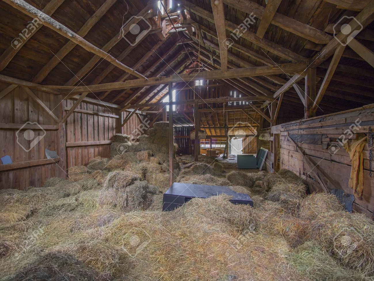 Old Post And Beam Barn Interior With Hay On The Floor Stock Photo