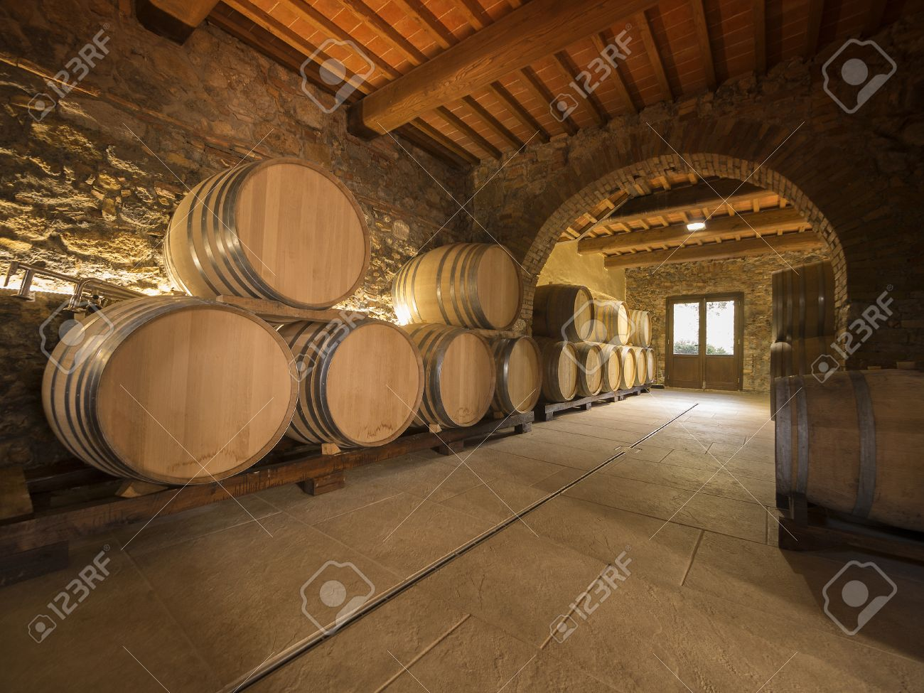 oak wine barrels. Oak Wine Barrels Stacked In A Winery Cellar Stock Photo - 23271395
