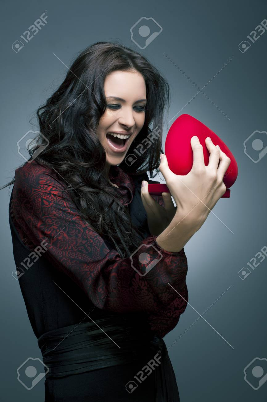 Valentine s Day  Beautiful smiling woman with a gift in the form of heart in his hands Stock Photo - 12844513