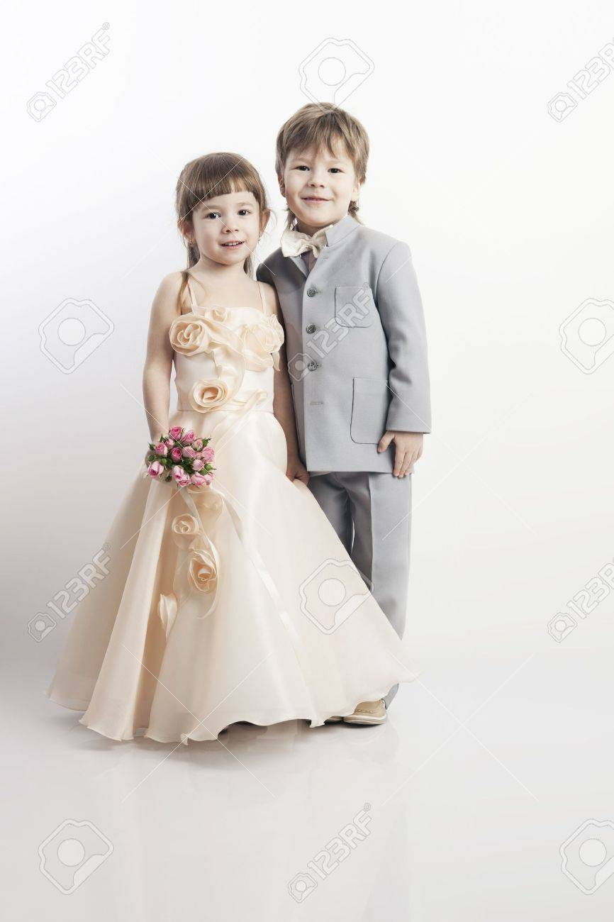 cf31d36c74 Portrait of two beautiful little boys and girls in wedding dresses from the  bridal bouquet on