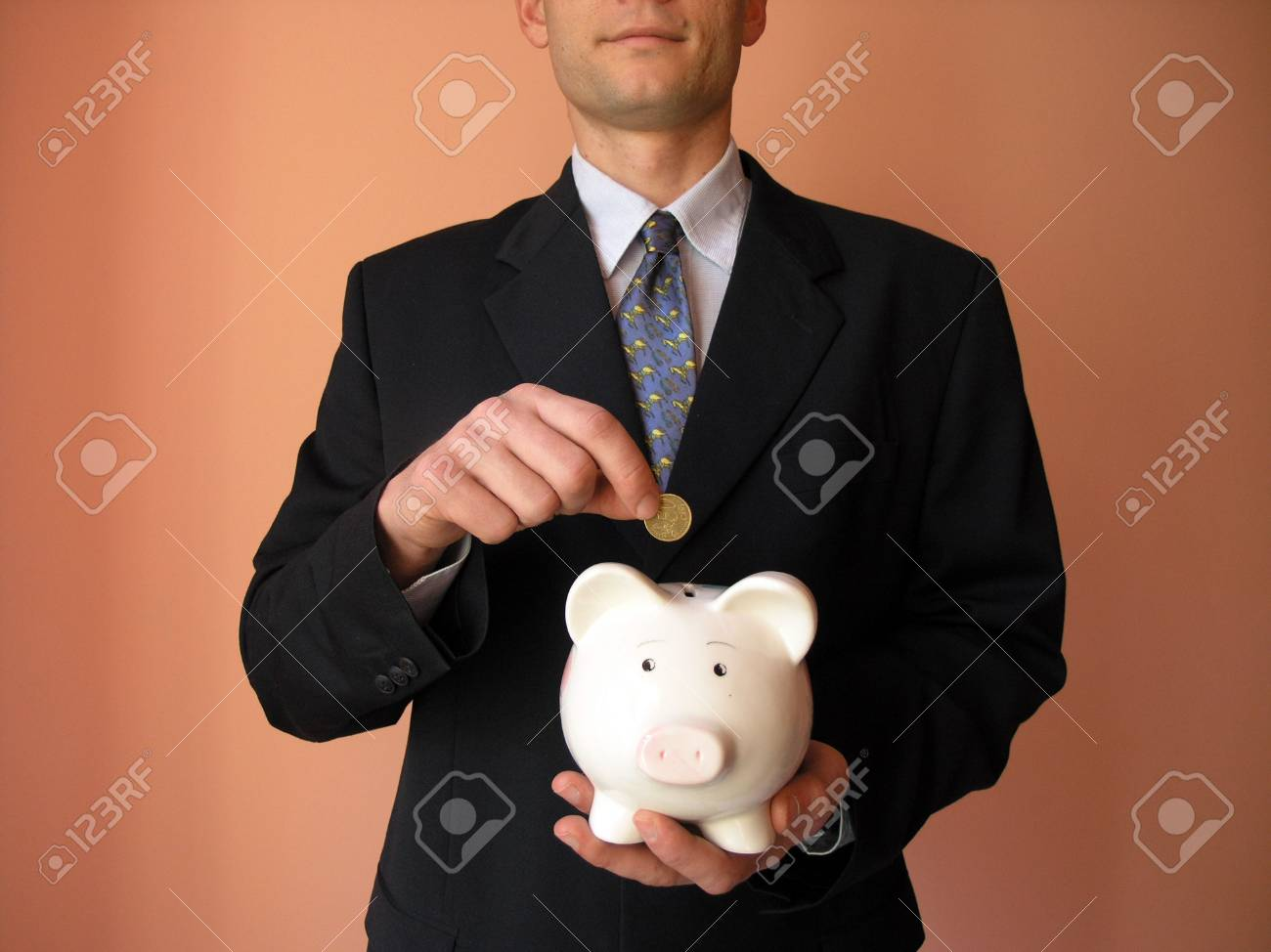 Businessman with a piggy bank.He puts coin in a piggy bank. Stock Photo - 2638763