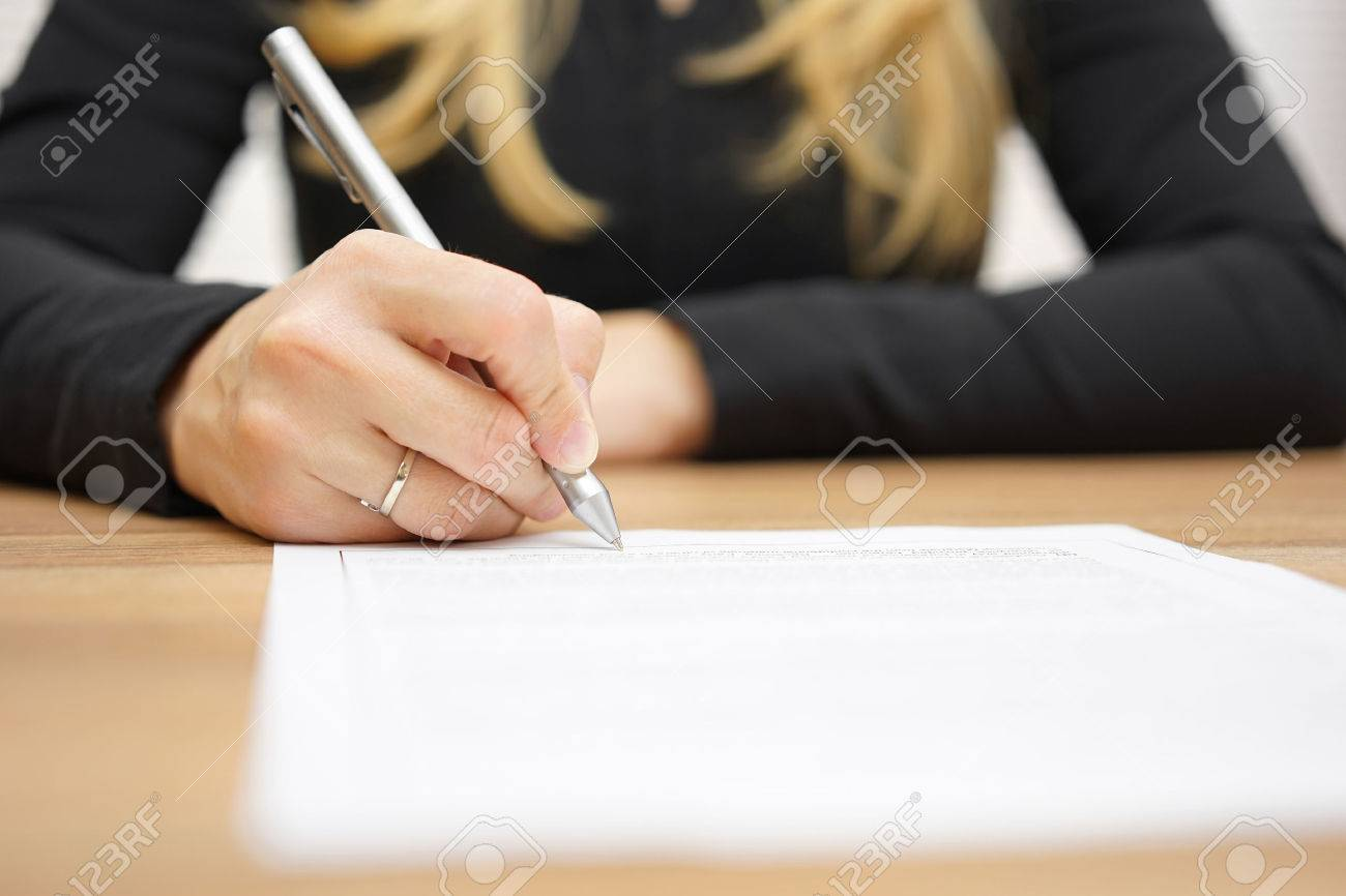 Woman With Black Shirt Is Signing Legal Document Stock Photo - Signing legal documents