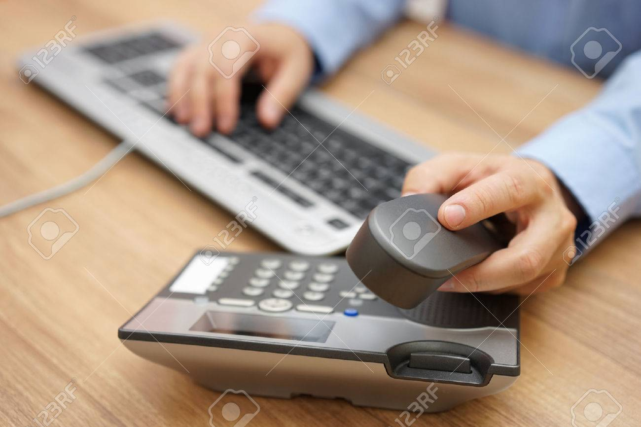 businessman hand picking up telephone receiver on business workplace Stock Photo - 44698476