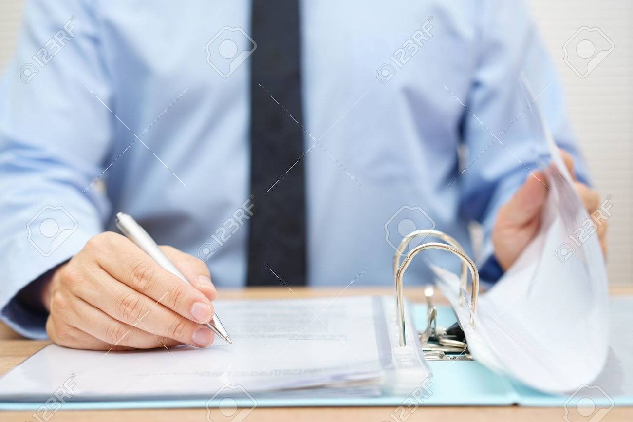 inspector is reviewing invoices in binder Stock Photo - 47707925