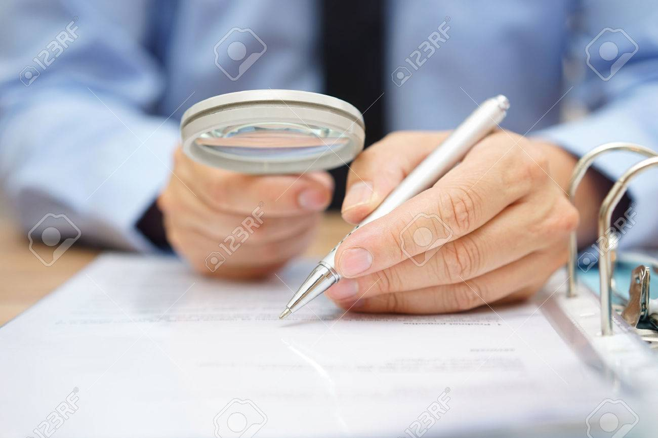 businessman is analyzing  through  magnifying glass contract and prices Standard-Bild - 47708393