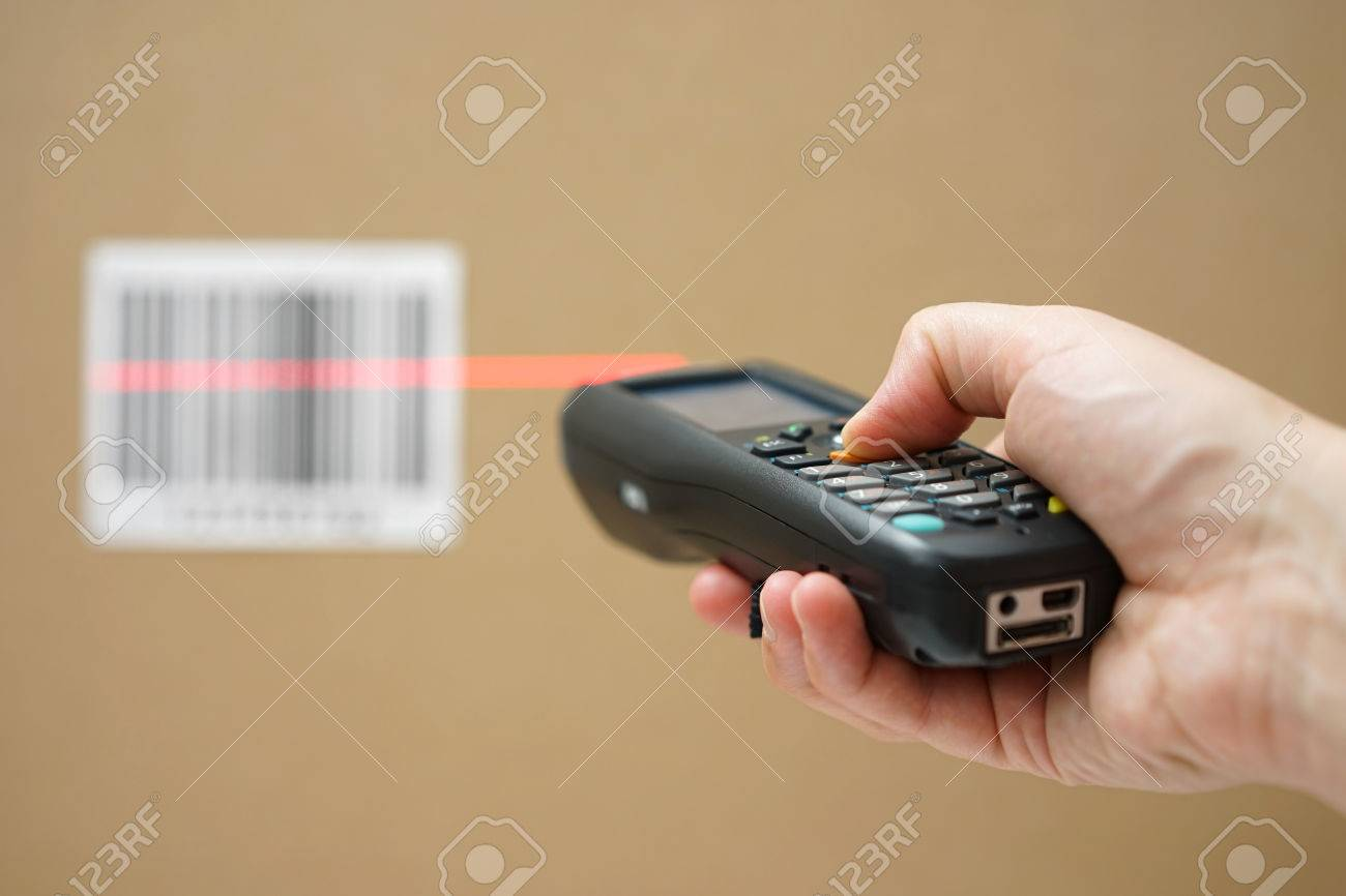 closeup of hand holding bar code scanner and scanning code on cardboard box Stock Photo - 47708400
