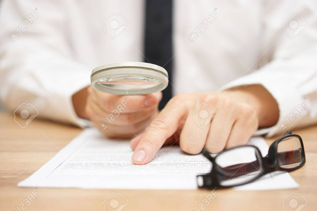Focused businessman is reading through  magnifying glass document Stock Photo - 47708428