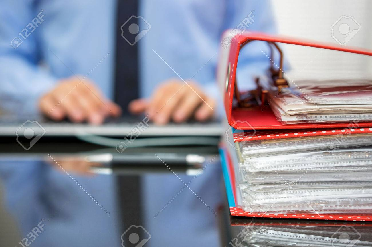 accountant with stack of invoices is inserting data into computer database Stock Photo - 47720491