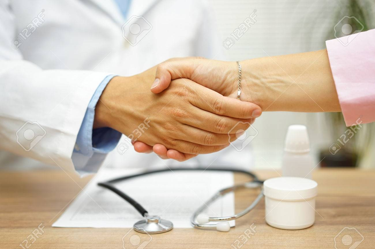 Satisfied patient is handshaking with good doctor over good health report Stock Photo - 54519428