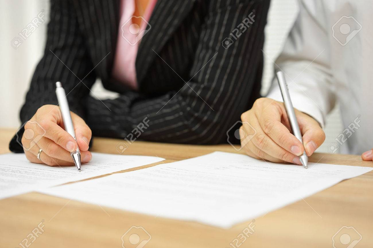 businesswoman and businessman signing contract in the office Standard-Bild - 54519499
