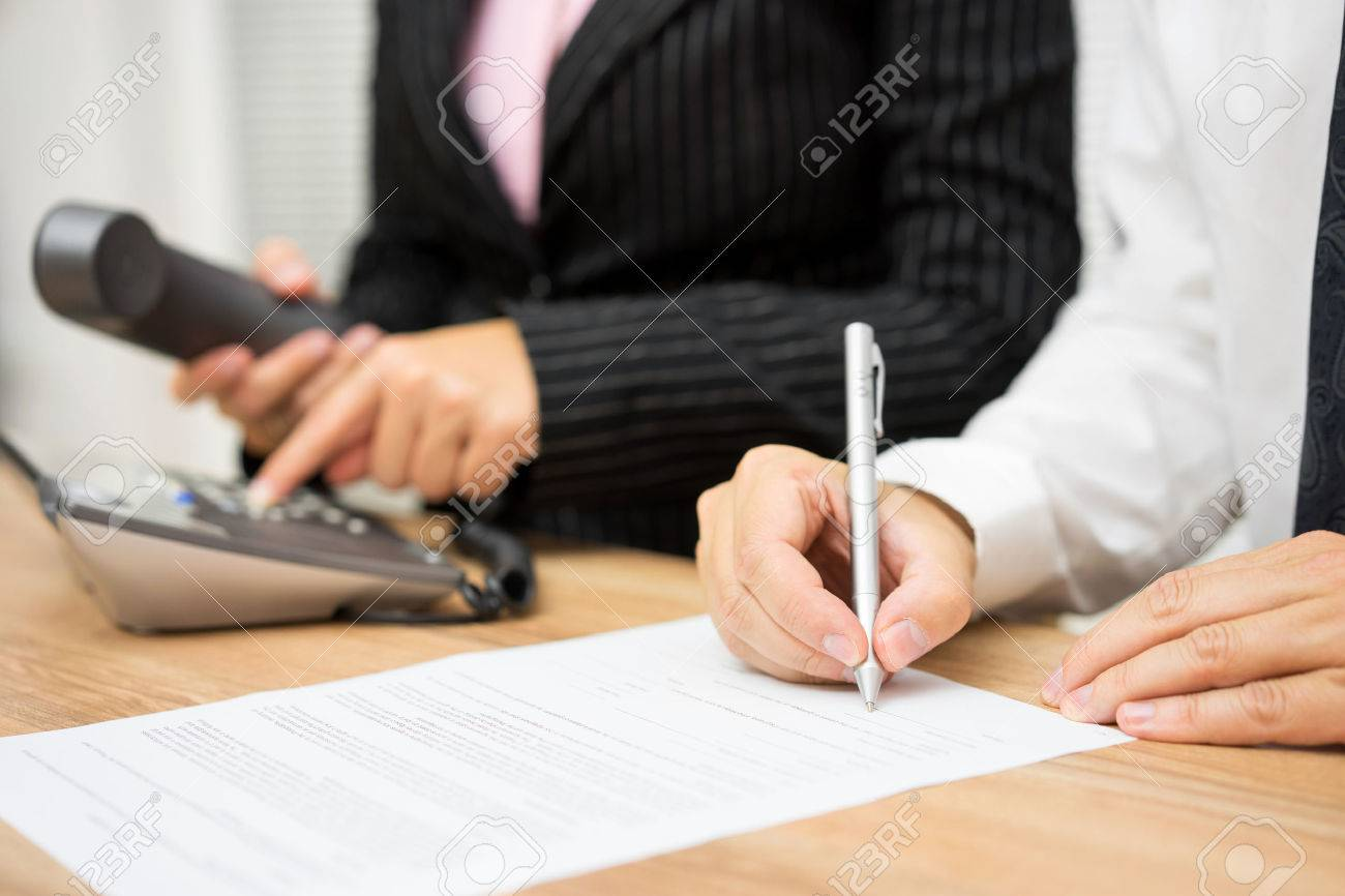 Business people are occupied with calling client or candidate and editing interview documents Standard-Bild - 54519918