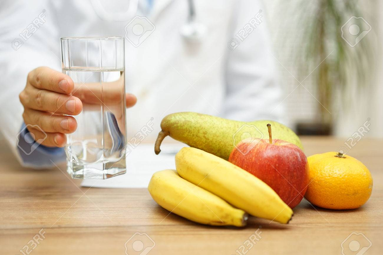 Doctor is offering water and fruit after reading diagnose. Healthy life and health care concept Standard-Bild - 54519937
