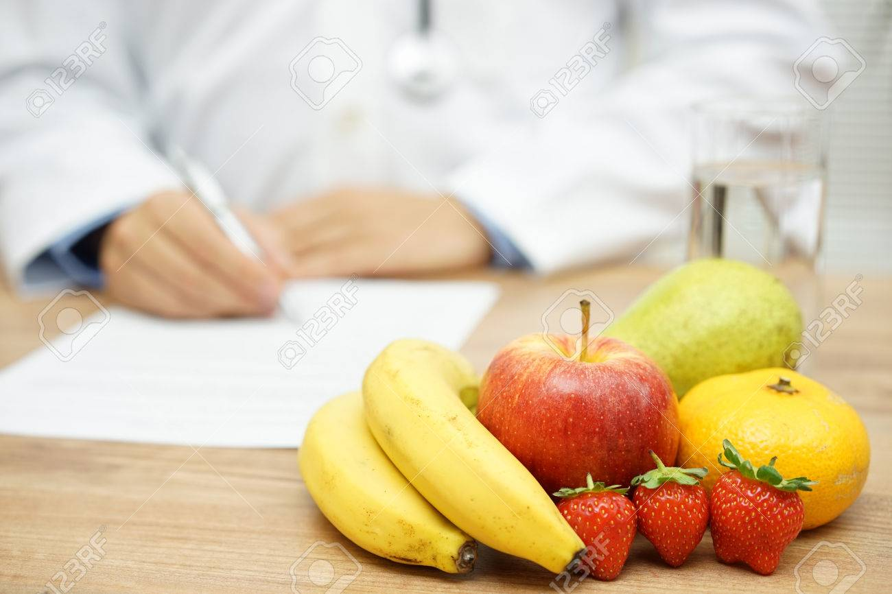 Nutritionist Doctor writing diet plan, focus on fruit and water Stock Photo - 56352940