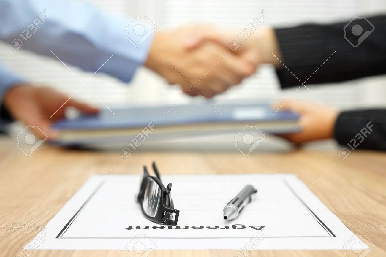 businessman and businesswoman are shaking hands and exchanging folder  after agreement was reached Standard-Bild - 56353061