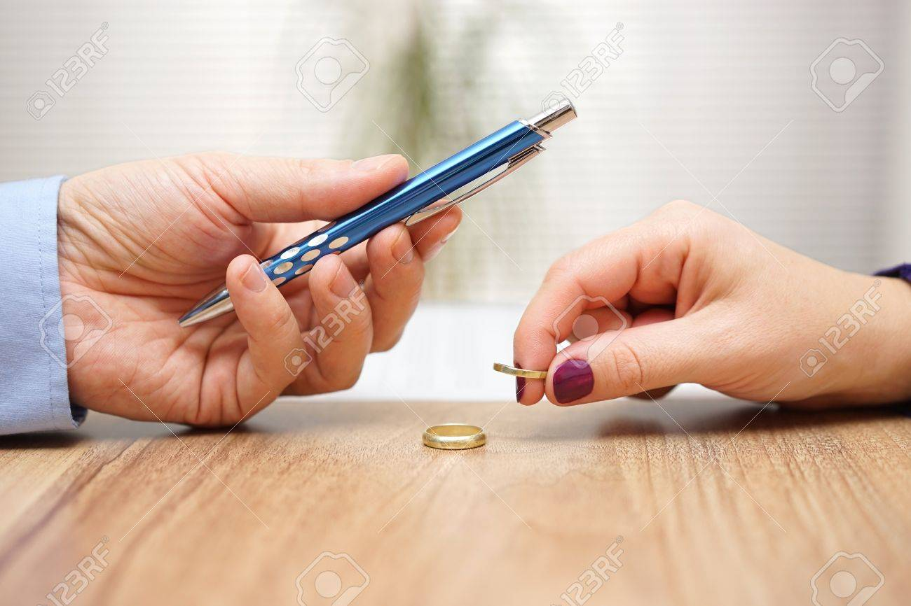 Husband is giving pen to sign divorce papers his former wife after he take off the ring form finger Standard-Bild - 56812635