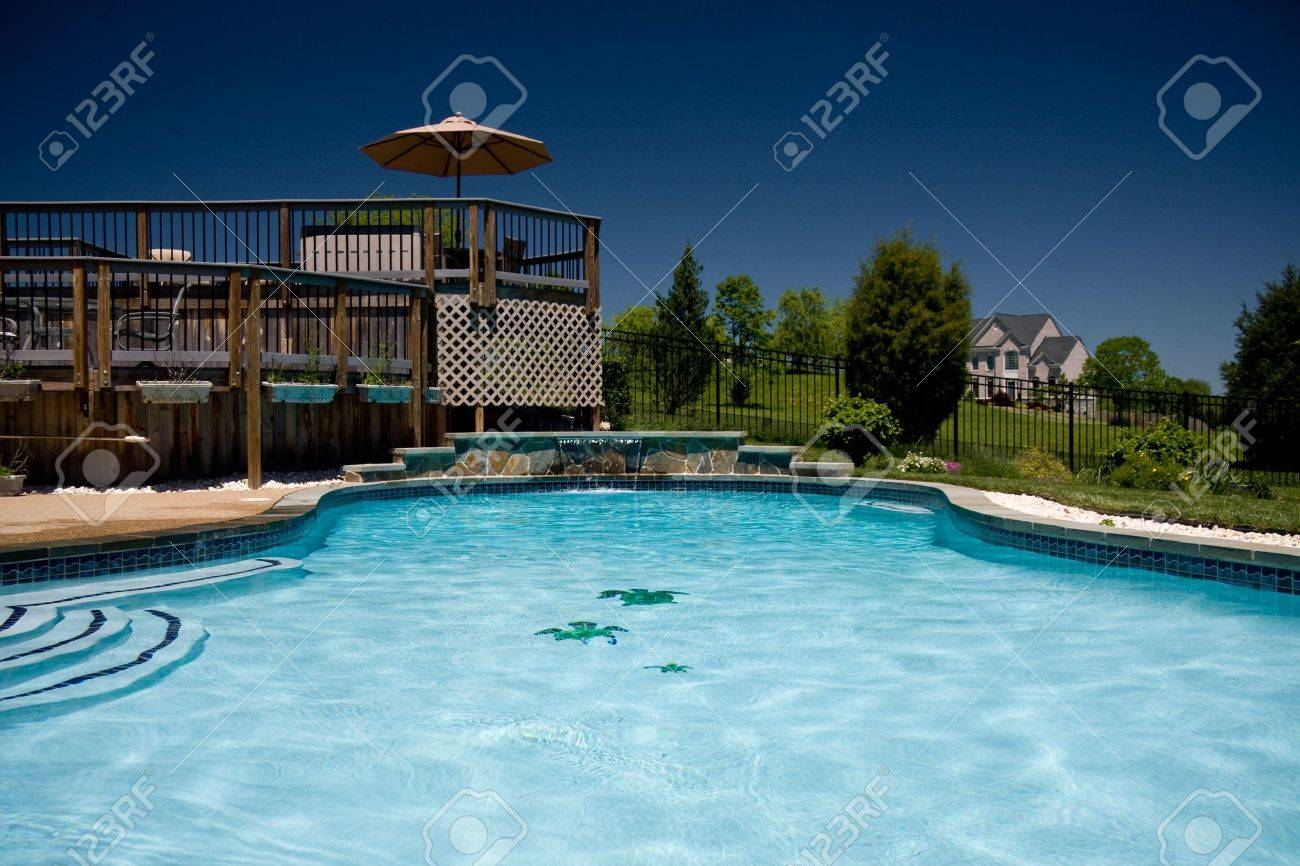 View of a backyard swimming pool with a deck taken from the water..