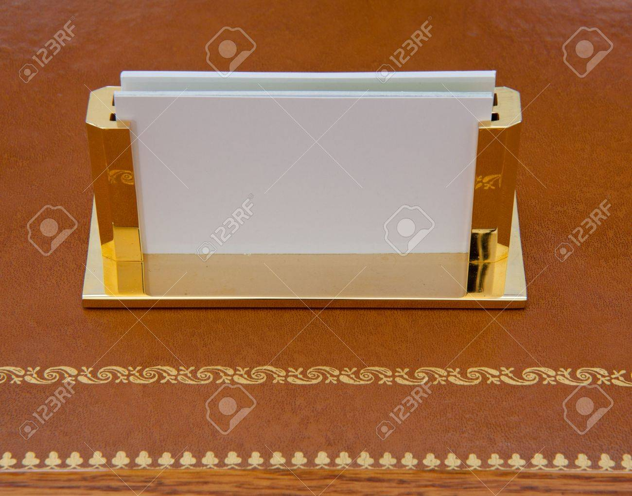 Brass business card holder on a leather desk with gold edging Stock Photo - 7282295
